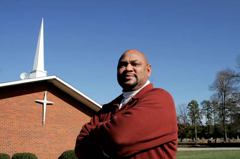 Omega Wilson, president of Mebane's West End Revitalization Association, stands in front of the historic church and cemetery that he and his neighbors have fought to save. Photo by Isaac Sandlin.