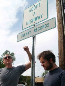 Photo by Catherine Rierson. Musician Ari Picker and Trekky Records' Martin Anderson show off Trekky's new Adopt-A-Highway sign, which can be found on North Greensboro Street.