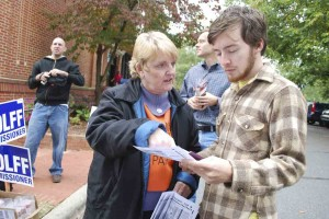 Photo by Ava Barlow. Elisabeth Scott, a volunteer for the Orange County Democratic Party, gives a sample ballot highlighting the Democratic candidates to Will Hackney of Chapel Hill. Hackney was on his way in to the Carrboro Town Hall to participate in early voting Saturday.
