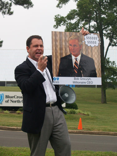 SEANC Executive Director Dana Cope holds up a photo of BCBSNC CEO<br /> Bob Greczyn as he exhorts health care reform advocates to band together. Photo by Taylor Sisk.