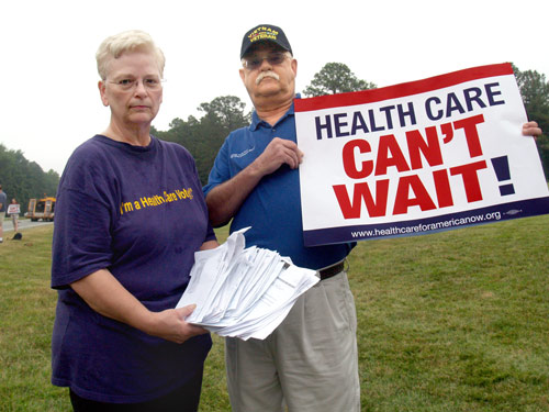 Cheryl Moon and Jerry Thompson display the medical bills that have driven Thompson into bankruptcy at a rally for health care reform held in front of Blue Cross Blue Shield headquarters on Wednesday. Photo by Taylor Sisk.