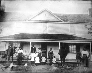 PHOTO COURTESY OF DOLORES CLARK. The Strayhorn family in front of their home, which still stands on Jones Ferry Road. This photo depicts the family in the 1930s. Toney Strayhorn was a master bricklayer, and the chimneys and their freestanding corbelled stacks showcase his expertise.