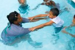 PHOTO BY BARBARA TYROLER. Oswaldo Reyes, 6, learns to swim with instructor Karysha Reid.