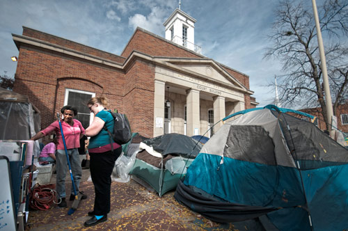 Amanda Ashley, a member of the Occupy Chapel Hill movement, gives a visitor to the Occupy camp information about the movement on Tuesday. 	Photo by Duncan Hoge