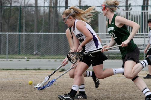 Carrboro's Ashley Prinzhorn fights Ravenscroft players for possession.