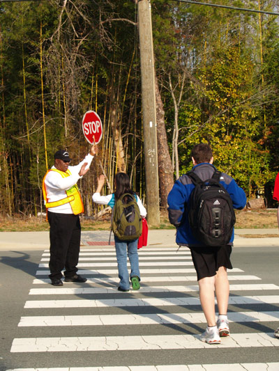 Longtime McDougle School crossing guard James Burnette greets students crossing Hillsborough Road in 2008. Burnette, who died last week at UNC Hospitals, will be sorely missed by the community.  Photo by Kirk Ross