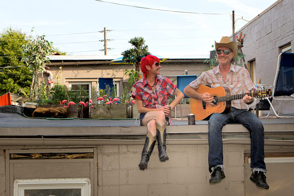 Rooftop living — Meg Davis and Ken Evans spend a summer evening at the edge of their rooftop living room above Cliff's Meat Market. Check out Meg and Ken in the Carrboro Community Resource & Visitors' Guide as well, inside this week's issue. PHOTO BY ALICIA STEMPER