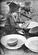 Native housewife sifting flour